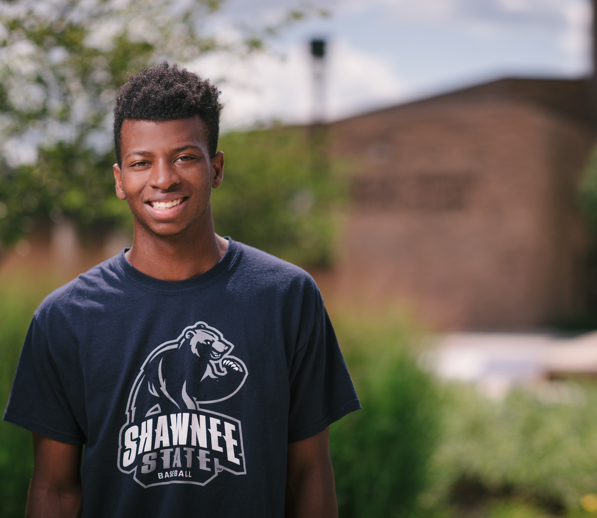 Male student smiling on campus in shawnee tshirt