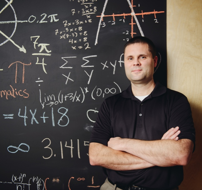 man in front of blackboard with calculations