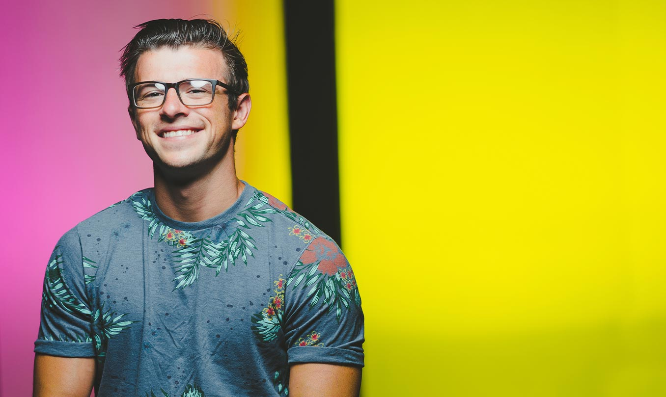 SSU Theatre student smiling on a pink and yellow background
