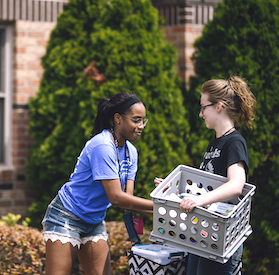 two female students carrying boxes at move-in