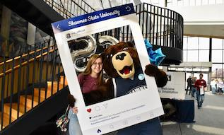 student posing for a photo with Shawn E. Bear at Orientation