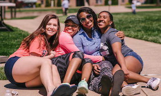 four female students hugging at picnic