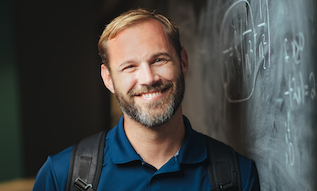 male student standing in front of chalkboard