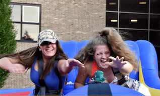 two female students playing on inflatables at Weekend of Welcome