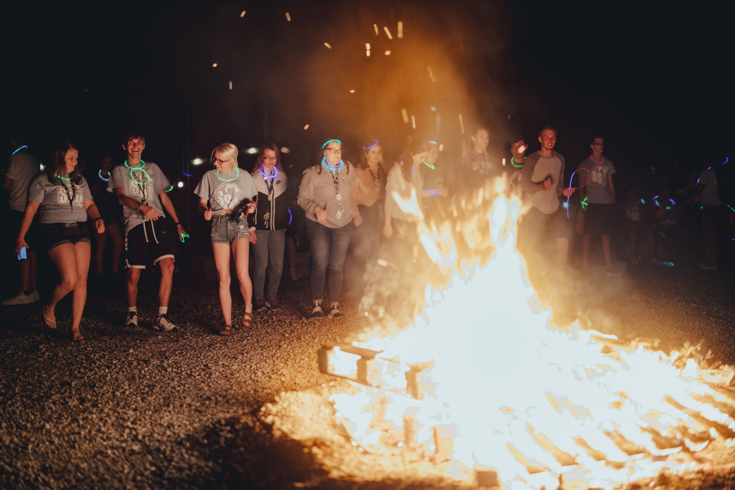 students dancing by bonfire