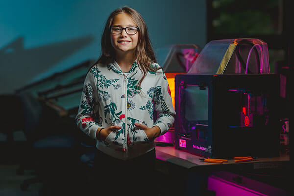 Middle School student in front of 3D Printer