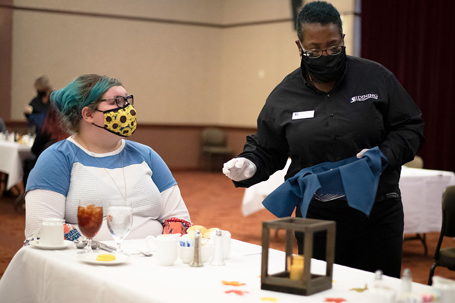 A masked student and server at a dinner table