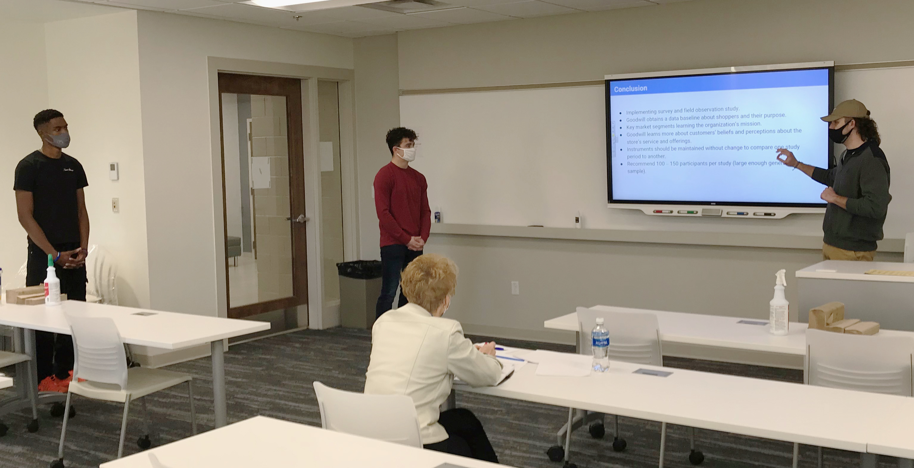 Tim Biakapia, Kade Tomlinson and Gavin Ogan present a consumer behavior proposal to Lenore Mason, Executive Director of Goodwill of Southern Ohio, Inc.