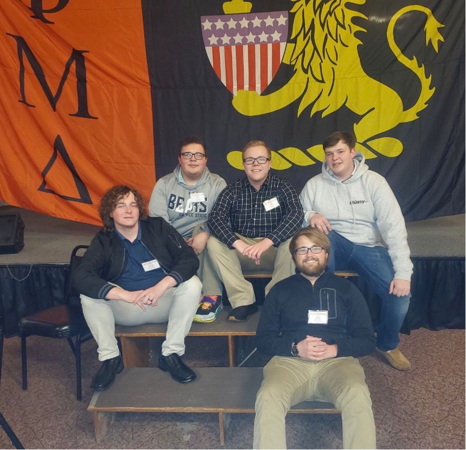 four male students in front of phi mu delta banner