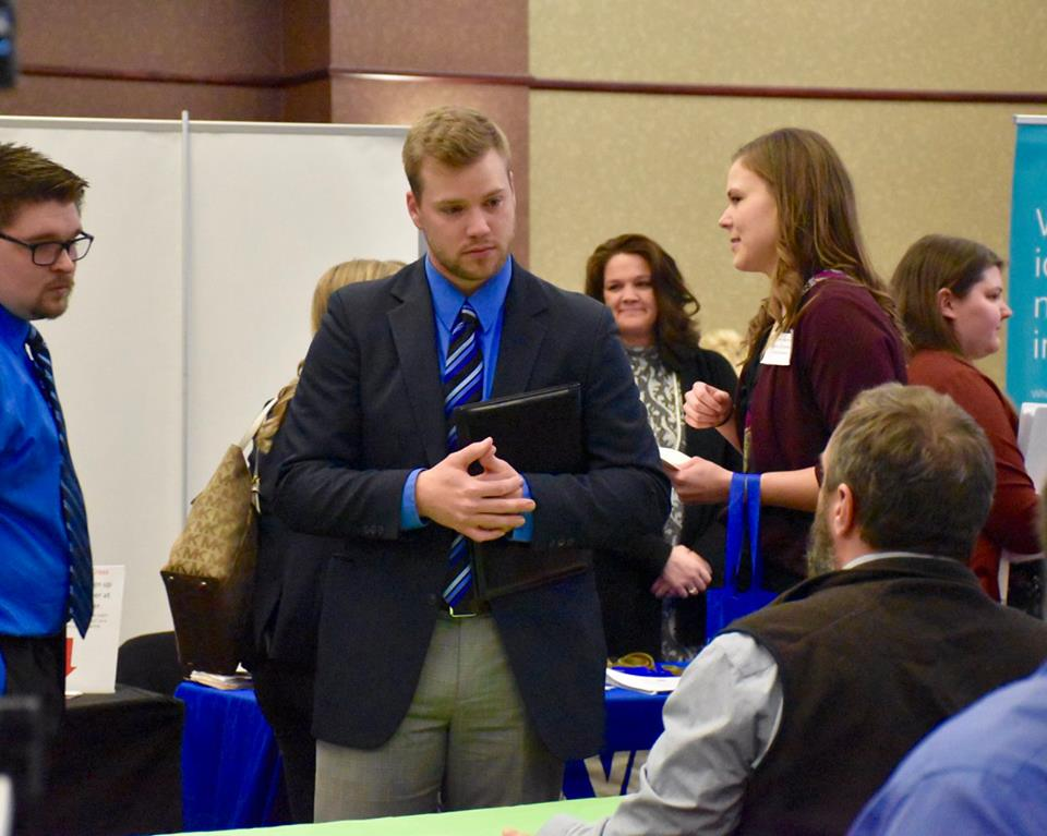 Career fair image showing students talking with employers.