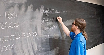 Student writing on a blackboard