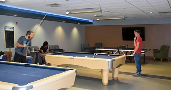 Two students playing pool in the recreation center
