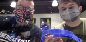 two students in masks holding face shields in plastics lab