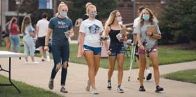Students in masks walking on campus