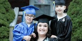 Woman with two boys in graduation regalia